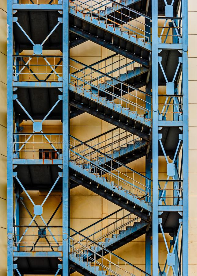 Tall concrete apartment block with repeating external fire escape stairs with metal railings. An tall concrete apartment block with repeating external fire stock images