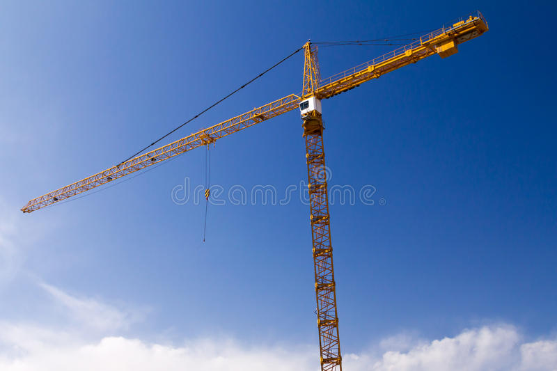 Tall construction crane against blue sky royalty free stock image