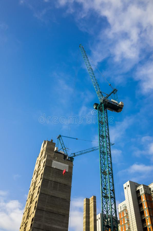 Tall crane operating on a constuction site of high-rise apartments in England, UK royalty free stock photos