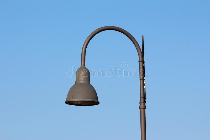 Tall dark grey modern public street lamp with LED light royalty free stock images