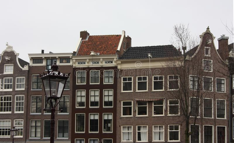Tall Dutch buildings built in red bricks in the style of Amsterdam. cold autumn day, gray and cloudy.  stock photo