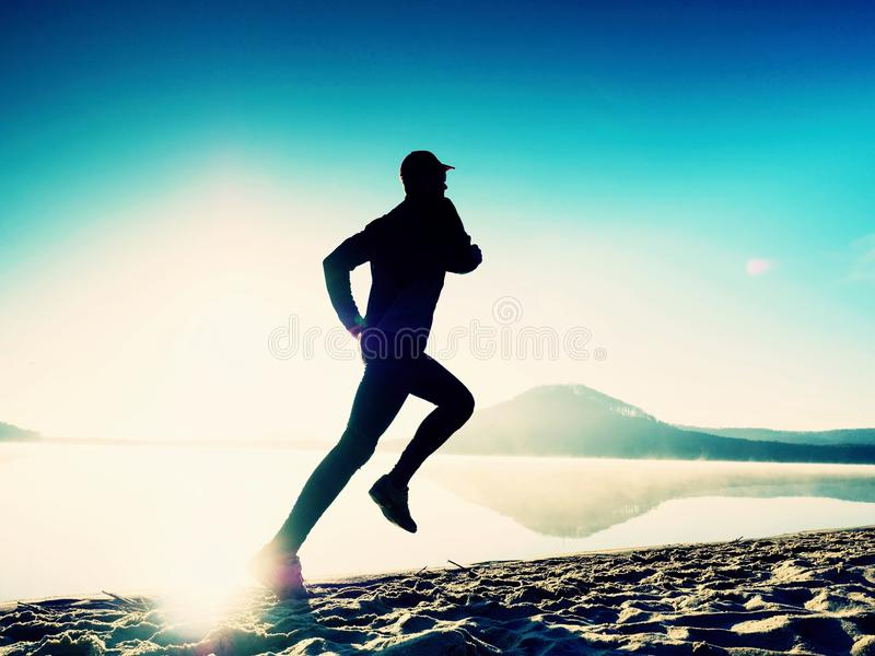 Tall fit man running along the sea shore in morning. Healthy male jogging on beach. royalty free stock image