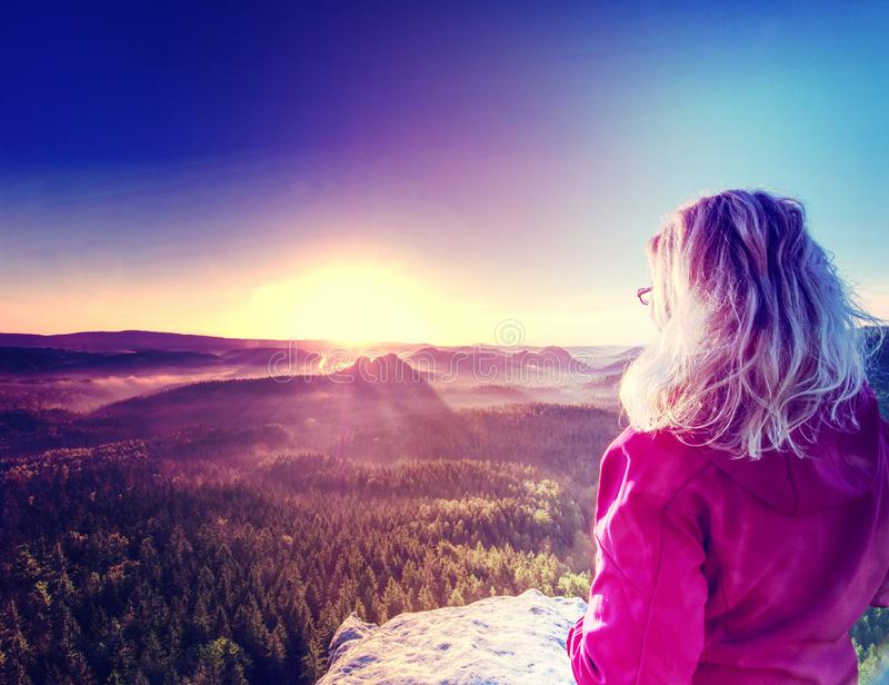 Tall girl tourist enjoy successful achievement of summit. With fantastic view into morning hilly landscape. Abstract filter, woman, warm, jacket, walking stock photo