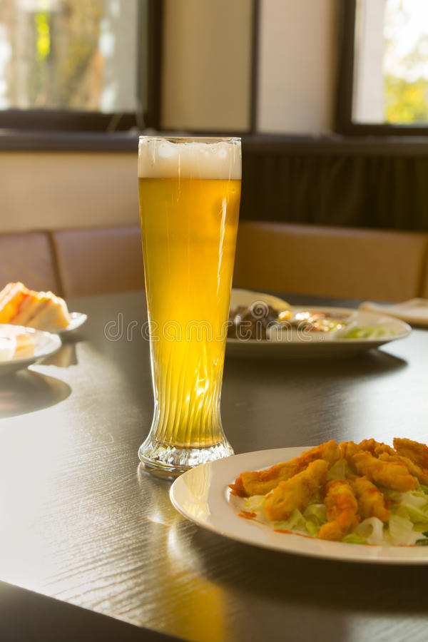 Tall Glass of Beer on Restaurant Table with Food royalty free stock photos
