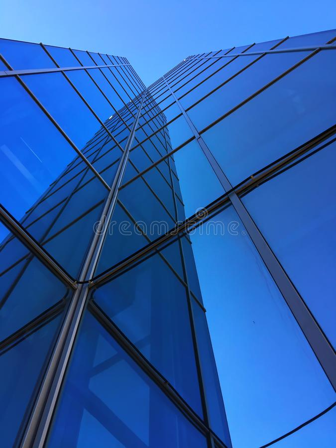 A tall glass building against a blue sky with reflection stock images