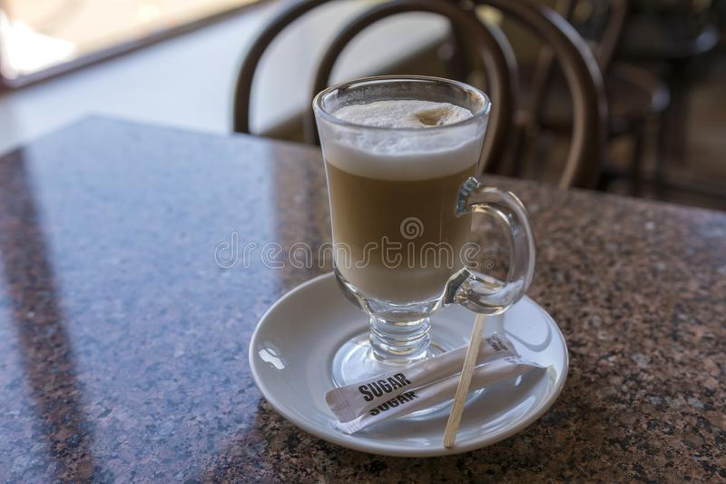 A tall glass of cappuccino on the table in the cafe.  royalty free stock images