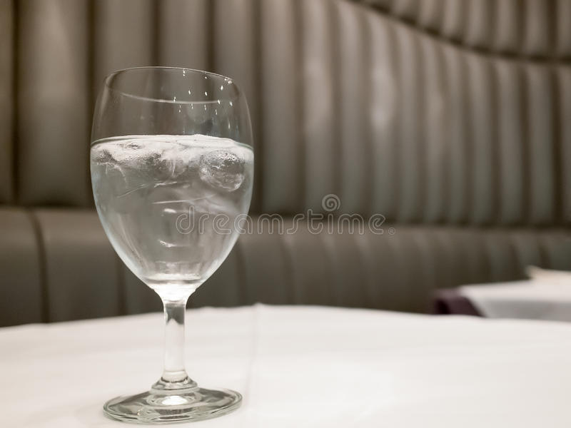 Tall glass fill by water and ice put on whit surface table in restaurant royalty free stock photos