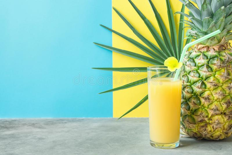 Tall Glass with Freshly Pressed Pineapple Orange Coconut Juice Straw and Small Flower. Round Palm Leaf on Blue Yellow Background stock image