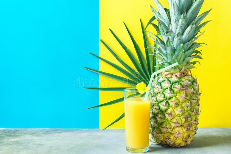 Tall Glass with Freshly Pressed Pineapple Orange Coconut Juice Straw Flower. Round Palm Leaf on Duotone Blue Yellow Background. Tall Glass with Freshly Pressed stock images