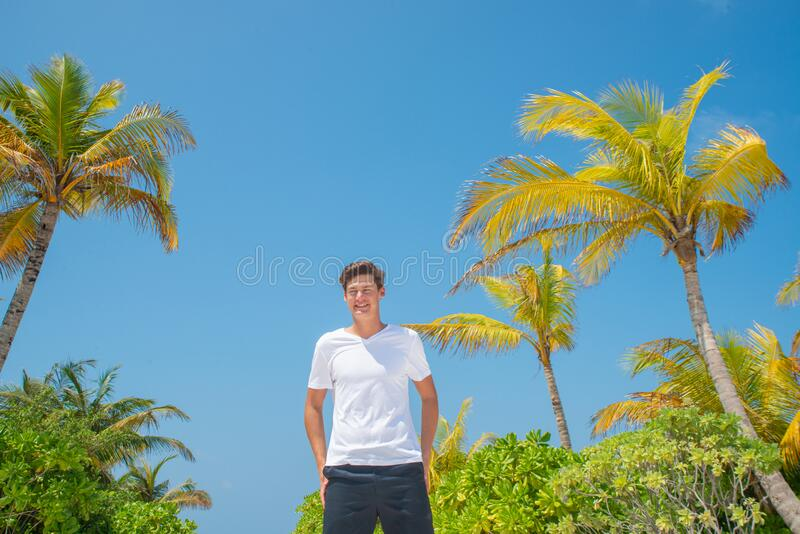 Tall handsome man wearing white t-shirt and black shorts standing at tropical sandy beach at island luxury resort stock photography