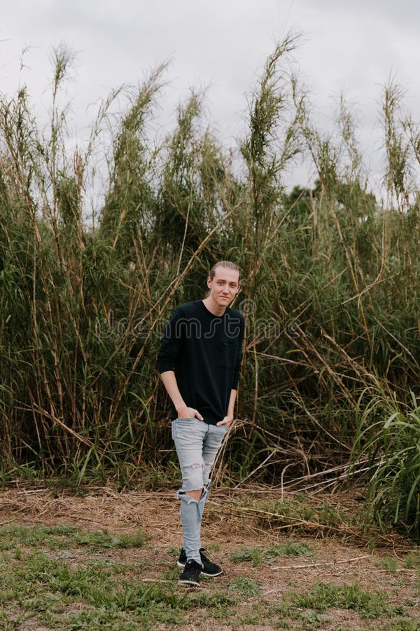 Tall and Handsome Young Man with Long Hair Pulled Back Modeling in Front of Very Tall Grass Outside in Nature. During the day royalty free stock photo