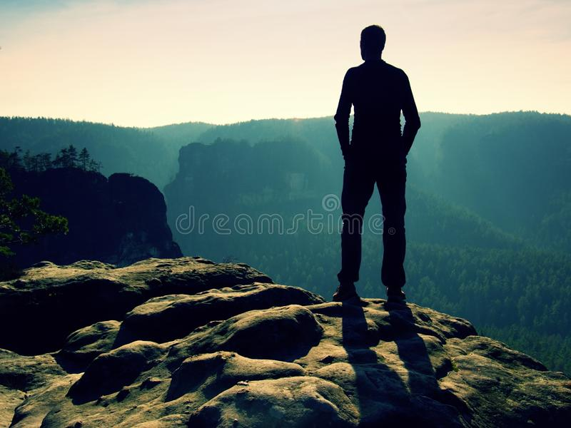 Tall hiker on peak of sandstone rock watching over the misty and foggy morning valley to Sun. Beautiful moment the miracle of natu. Tall hiker stand on the peak royalty free stock photos