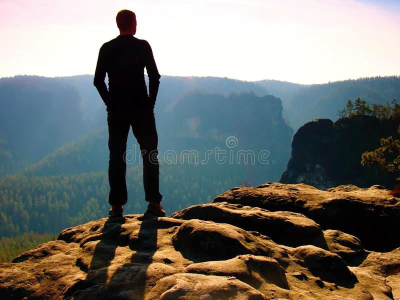 Tall hiker on peak of sandstone rock watching over the misty and foggy morning valley to Sun. Beautiful moment the miracle of natu. Tall hiker stand on the peak royalty free stock photo