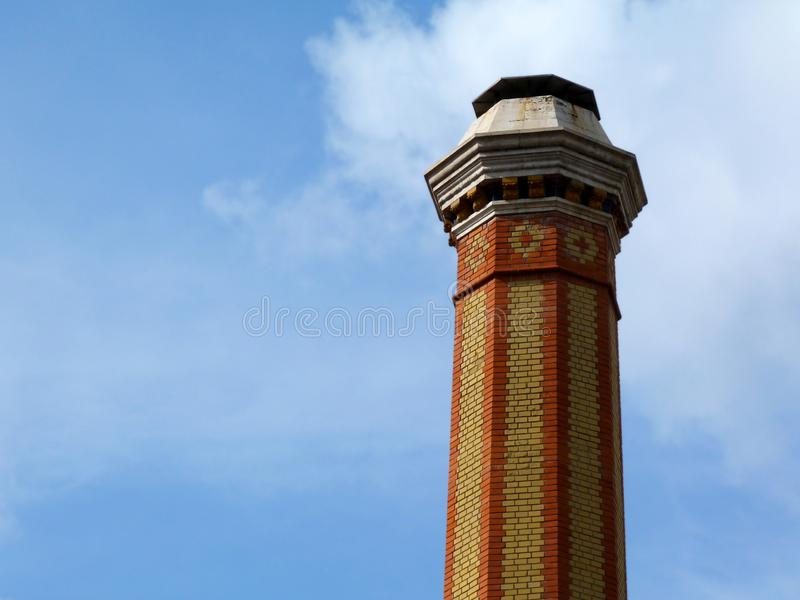 Tall industrial chimney stack of yellow and red brick of octagonal base. Decorative tall industrial chimney stack of yellow and red brick of octagonal base and royalty free stock photo