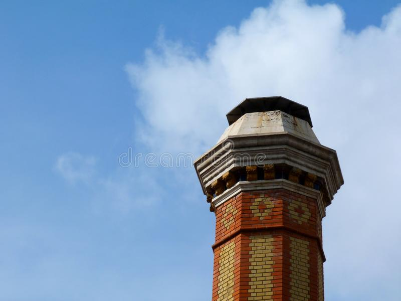 Tall industrial chimney stack of yellow and red brick of octagonal base. Decorative tall industrial chimney stack of yellow and red brick of octagonal base and stock photography