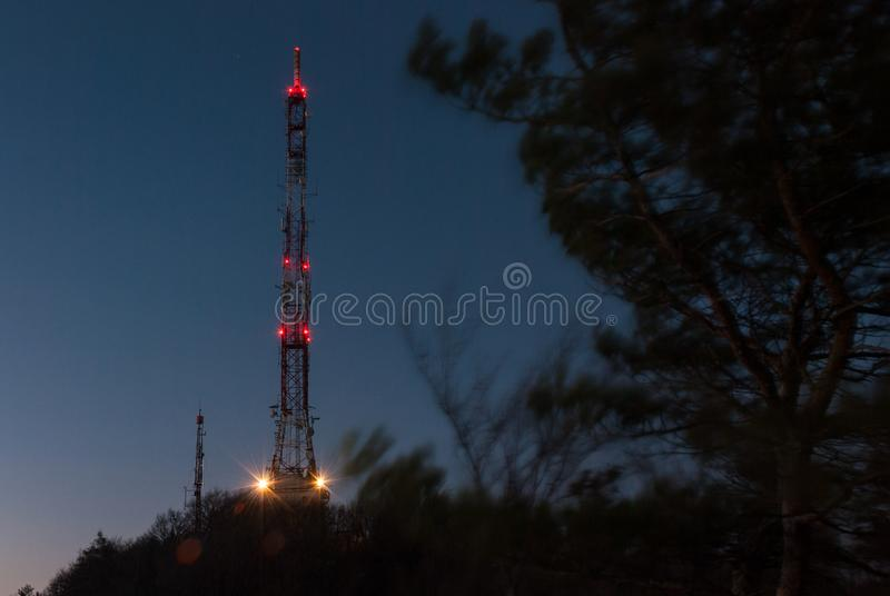 Tall lattice telecommunication tower with aviation lights. Tall lattice telecommunication tower with microwave antennas and aviation lights in the night sky royalty free stock images