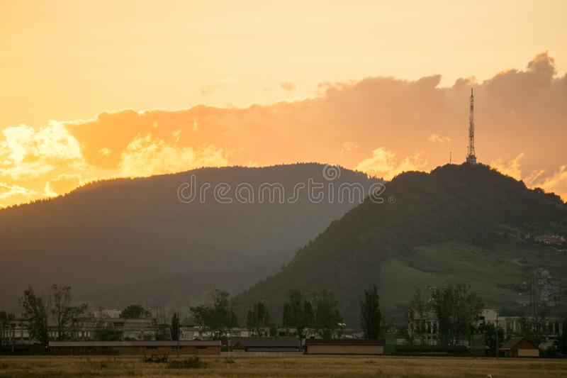 Tall lattice telecommunication tower at sunset. Tall lattice telecommunication tower on mountain at sunset royalty free stock image