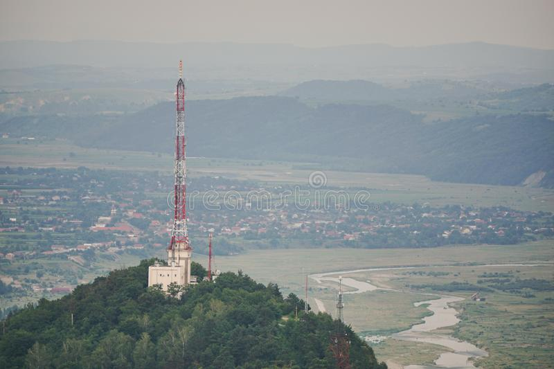 Tall lattice telecommunication tower on mountain. Above city in the summer royalty free stock images