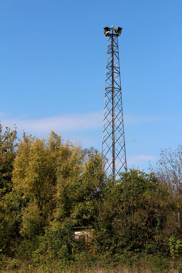 Tall metal structure holding four large public civil defence warning air sirens above small completely overgrown structure and. Dense forest on clear blue sky stock images