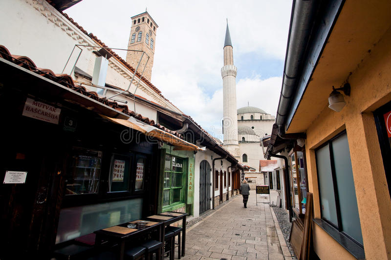 Tall minaret tower in the historical street. SARAJEVO, BOSNIA AND HERZEGOVINA: Tall minaret tower in the end of the historical street of bosnian capital. In 2013 royalty free stock photos