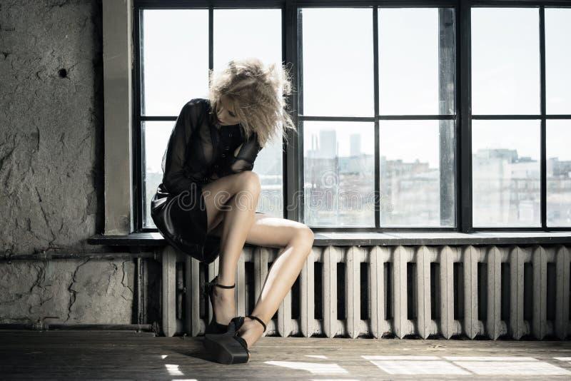 Tall model sitting on the windowsill in dark midi leather skirt stock photo