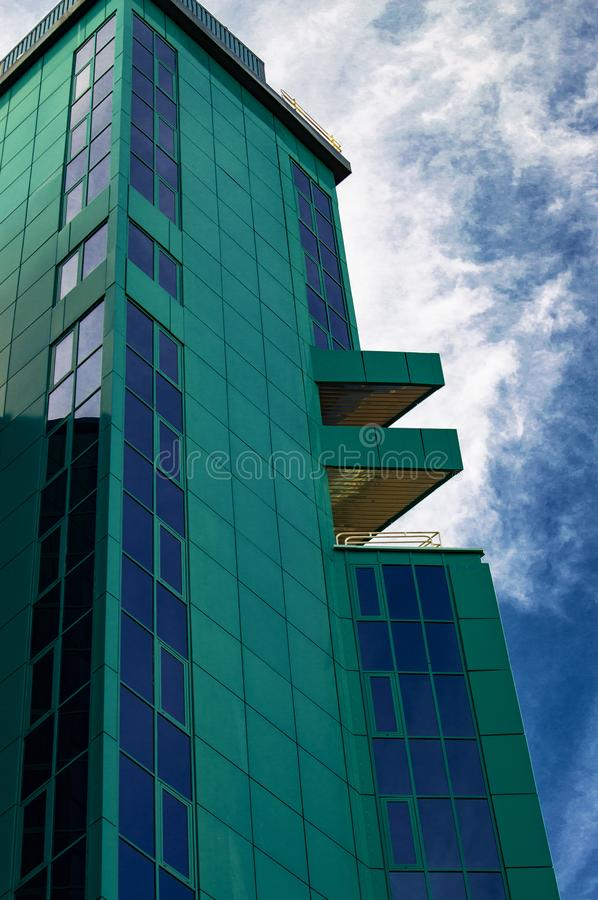A tall office building in green against a blue sky and white clouds. View from below royalty free stock images