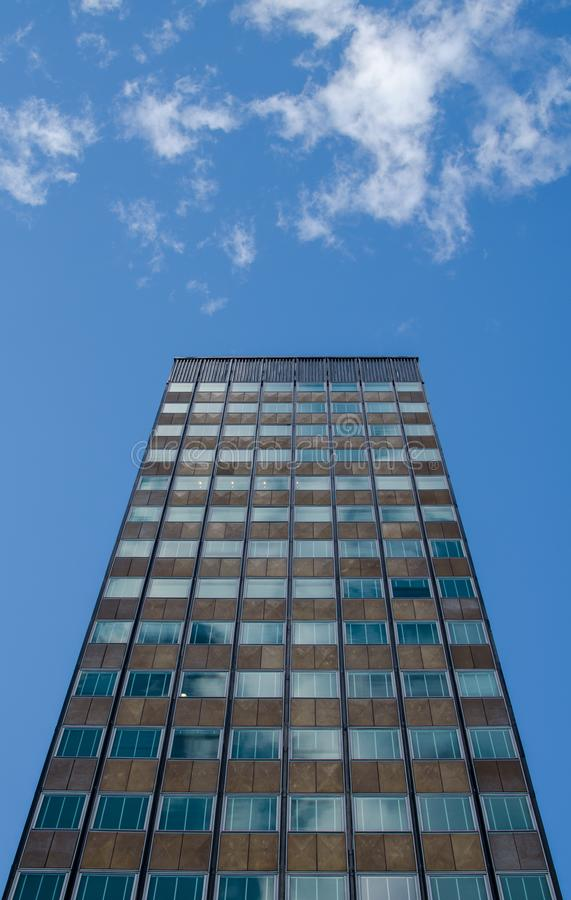 Tall office building standing alone beneath a sunny blue sky with a couple of coulds. A tall office building stands alone under a beautiful blue sky. The shot is stock photography