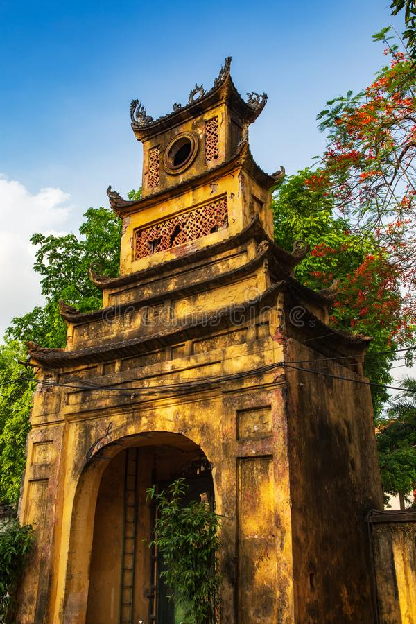 Tall old yellow gate surrounded by trees in the Thang Long Citadel in the imperial city, Hanoi, Vietnam. Tall yellow gate surrounded by trees with flowers in the royalty free stock images