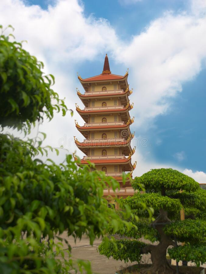 Tall pagoda at Vinh Trang temple, near My Tho, Vietnam. Low angle view from the gardens. Tall pagoda at Vinh Trang temple, near My Tho, Vietnam. Low angle view stock image