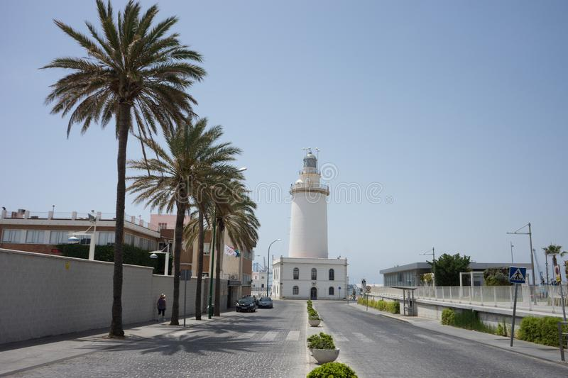 Tall palm trees in front a white lighthouse at Malagueta beach i. N Malaga, Spain, Europe on a bright summer day with clear skies stock photo