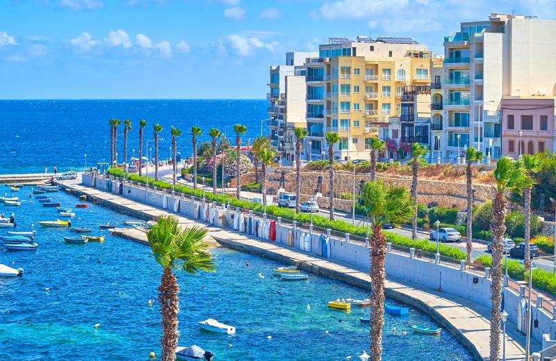 The tall palms at Dawret Il-Gzejjer seaside promenade. The main walking street of Bugibba resort, overlooking St Paul`s Bay with fishing boats, Malta stock photos