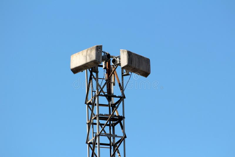 Tall partially rusted strong metal tower with two old antennas mounted on top on clear blue sky back stock photography