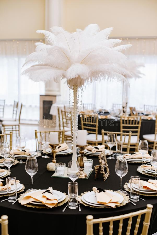 A tall pedestal with white feathers on the holiday table. Stylish decoration. Of the wedding banquet in golden and black tones royalty free stock photo