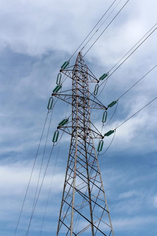 Tall power line utility pole made of metal pipes with multiple electrical wires connected with glass insulators on cloudy blue sky stock photos