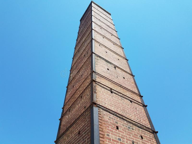 Tall red brick chimney or masonry with metal support stock images