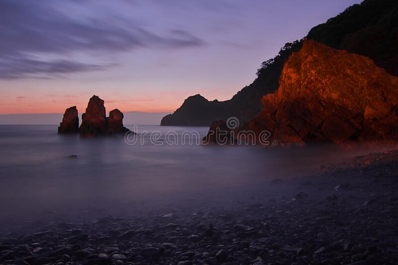 Tall Rock Formation Submerged in Water Near the Shore during Golden Hour stock images