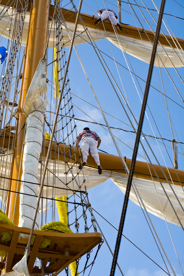 Tall ship. Two young sailor climb on a school ship royalty free stock image