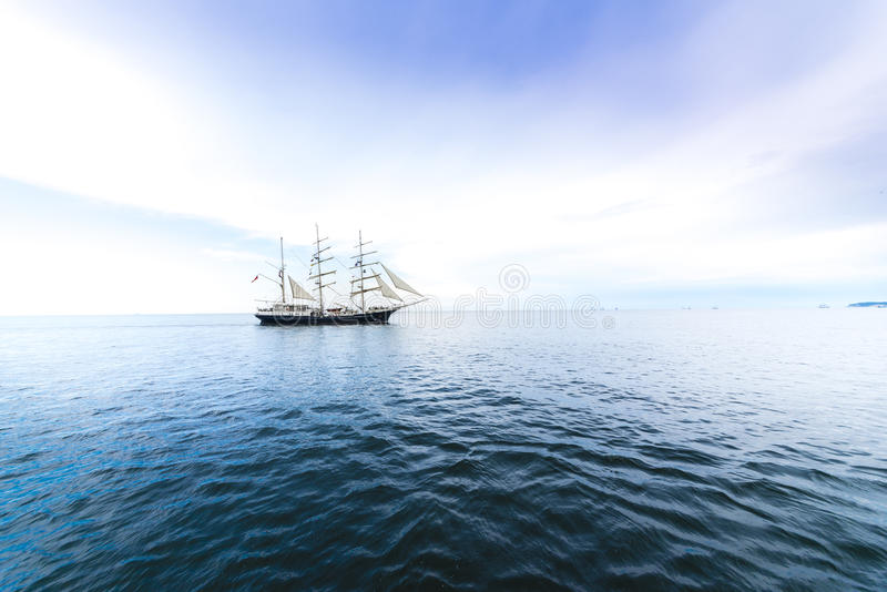 Tall ship on blue water. stock photos