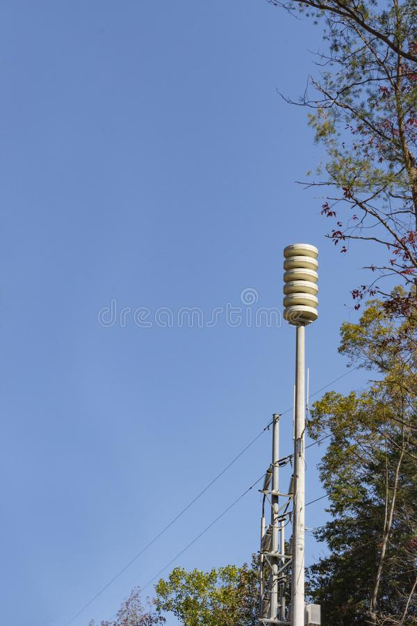 Tall siren tower beside trees with blue sky, space for text. Vertical aspect stock images