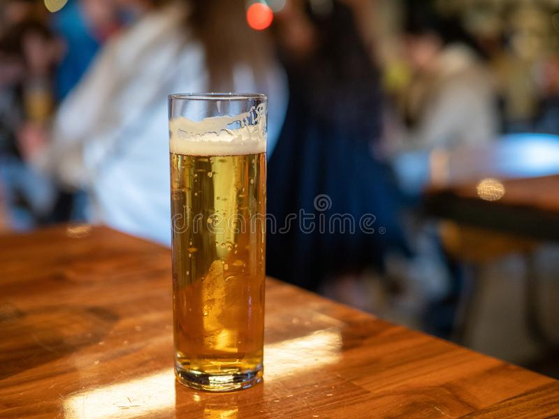 Tall skinny glass of golden lager beer sitting on bar counter royalty free stock photos