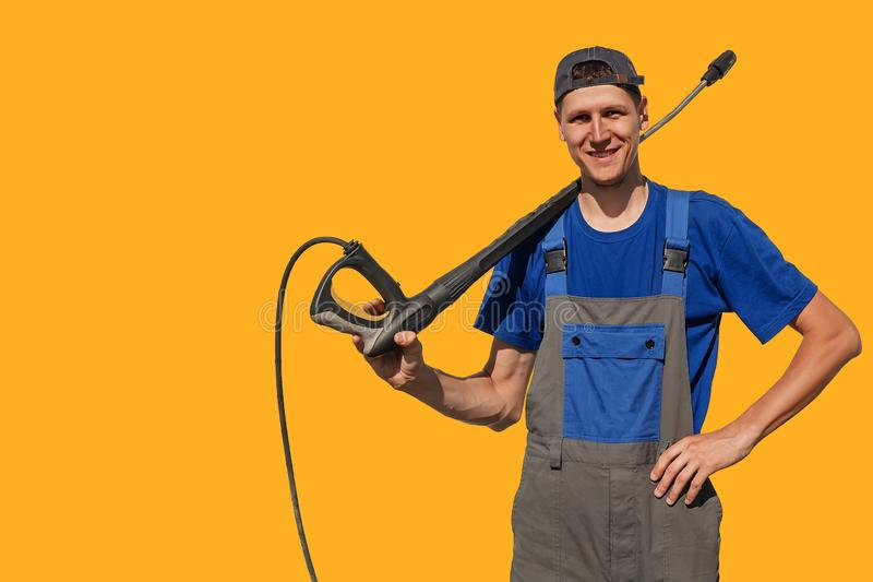 Tall slim guy with a gun for a car wash isolated on yellow background. A worker in coveralls looks at the camera and smiles. Background or layout with space royalty free stock photos