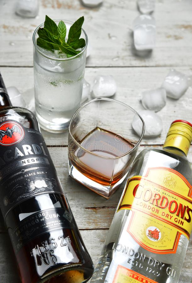 Tall and squad glasses of strong alcohol and two bottles  on wooden table surrounded by ice cubes royalty free stock photo