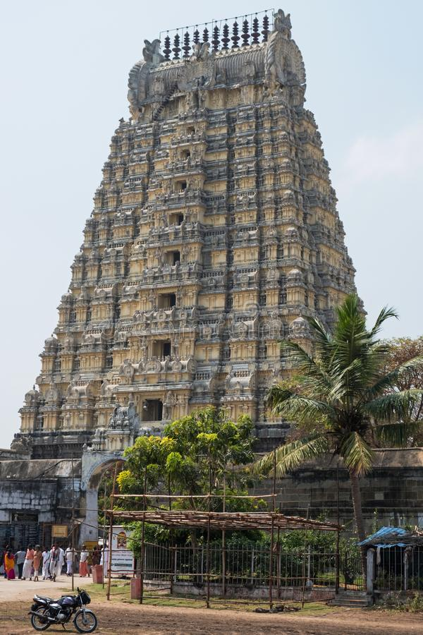 Tall temple gateway at Kanchipuram, India. Kanchipuram, India - March 18, 2018: Devotees pass through the Gopuram, or gateway tower, at the entrance to the stock photos