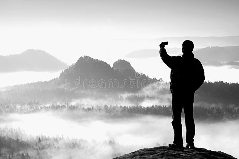 Tall tourist is taking selfie on peak above valley. Smart phone photography stock images