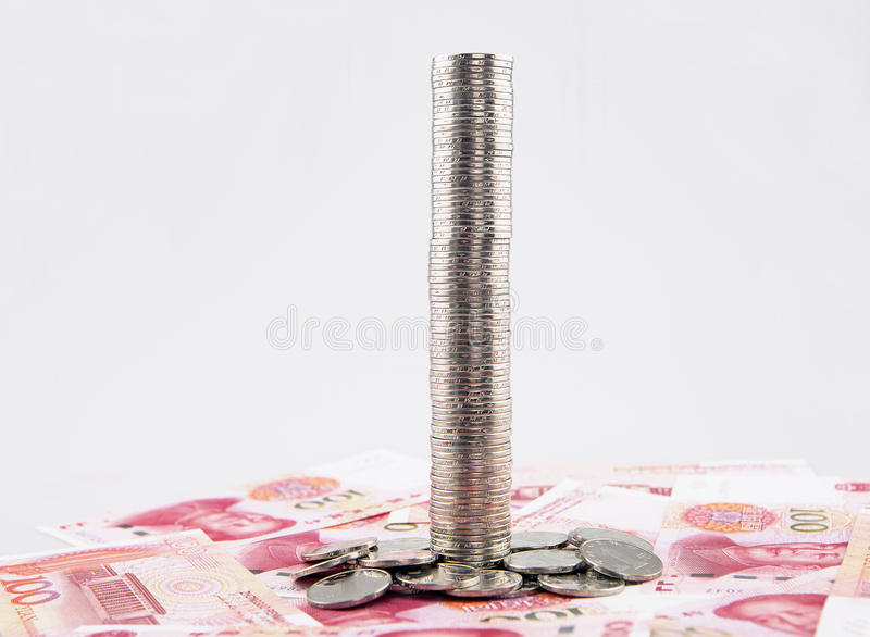 Tall tower of coins with china yuan banknotes royalty free stock photography