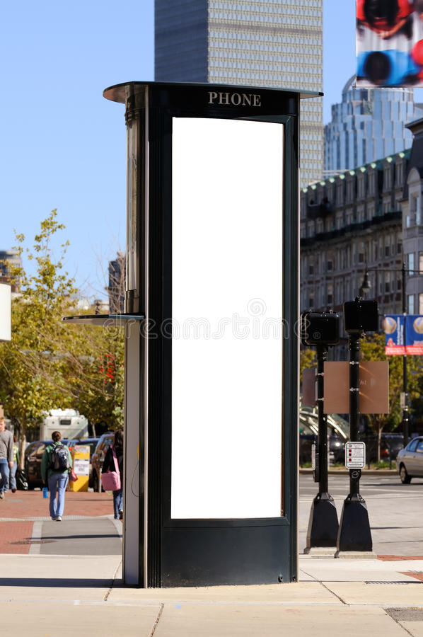 Tall, vertical billboard on phone booth stock photography