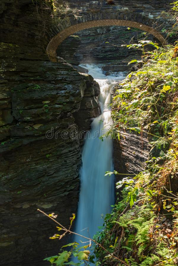 Tall waterfall cascading into Glen creek in Watkins Glen state park, New York. View from Gorge trail royalty free stock photography