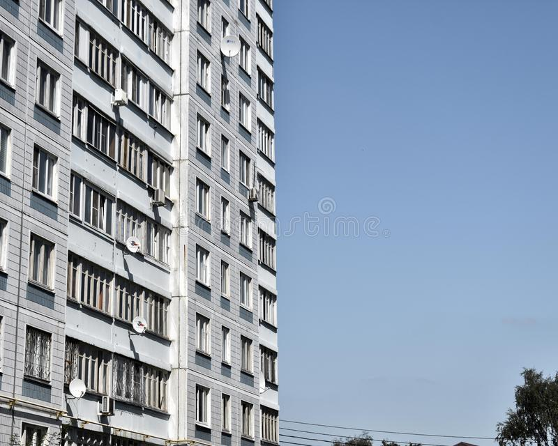 Tall white apartment building on the left with blue sky on the right with space for text stock photography