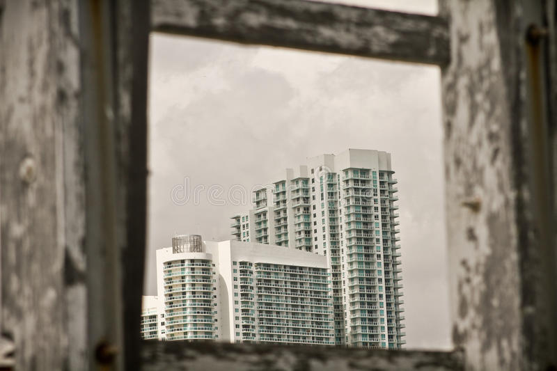 Tall white buildings. An urban view of tall white multi-story buildings framed by weathered wood stock photo
