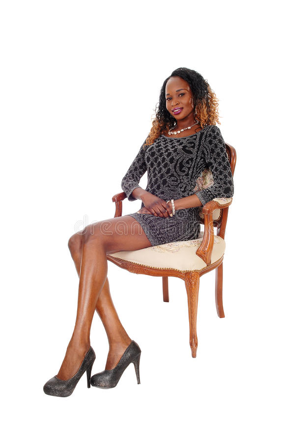 Tall young lady sitting in armchair. royalty free stock photography